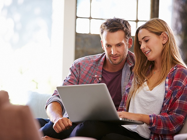 young couple wearing flannel on computer