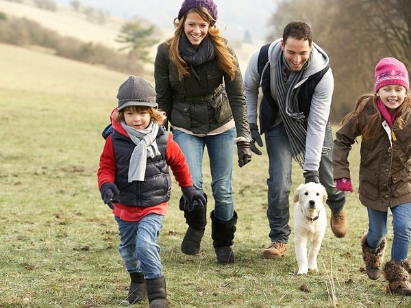 young family walking up fall hill with dog